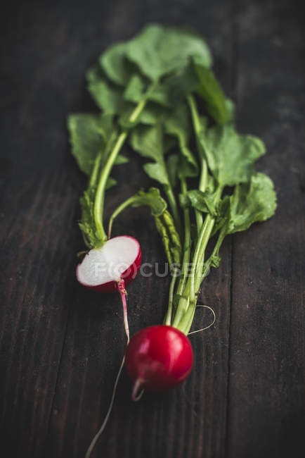 Whole and halved red radishes — Stock Photo