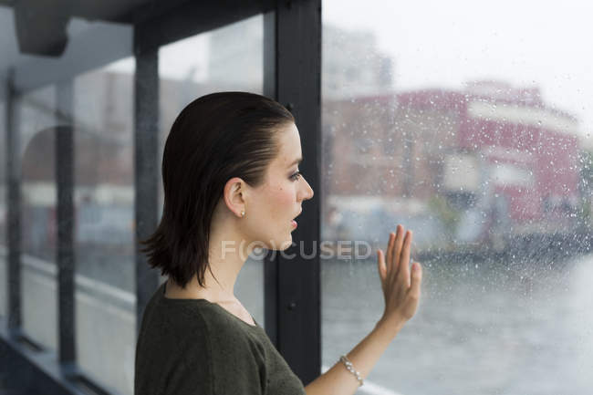 Young woman looking through window of an excursion boat on a rainy day — Stock Photo