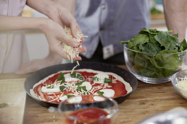 Pareja preparando pizza en la cocina - foto de stock