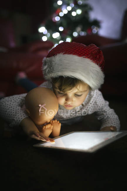 Little girl wearing Christmas cap using digital tablet at home — Stock Photo