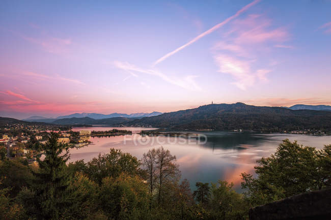 Austria, Carinthia, Poertschach, lake and trees on shore at sunset — Stock Photo