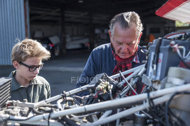 Grandfather and grandson repairing biplane — Stock Photo
