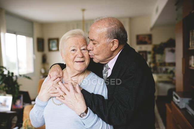 Senior couple hugging and kissing at home — Stock Photo