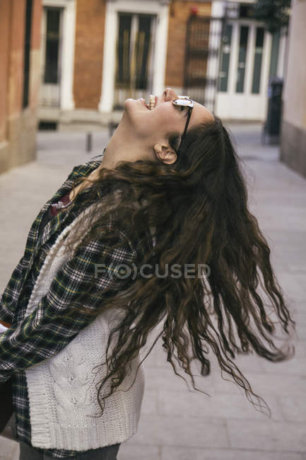 Laughing young woman with long brown hair wearing sunglasses — Stock Photo