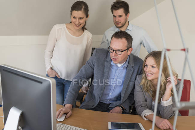 Quatre collègues au bureau regardant l'écran d'ordinateur — Photo de stock