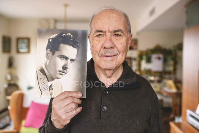 Portrait of senior man showing an old picture of himself — Stock Photo
