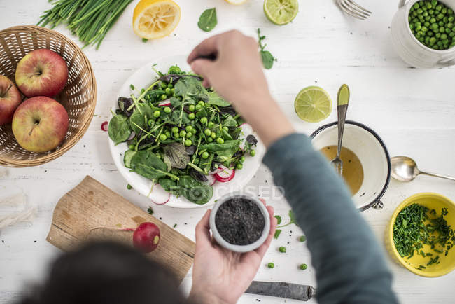 Cropped view of person preparing salad with seasoning of black sesame — Stock Photo