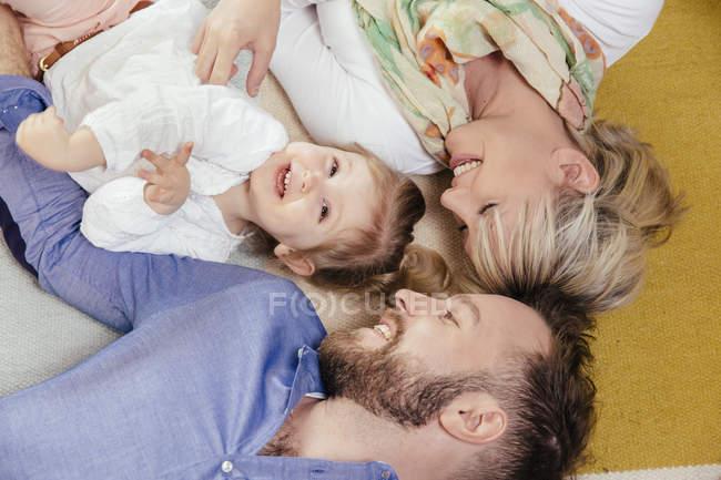 Família de três deitado no tapete em casa — Fotografia de Stock