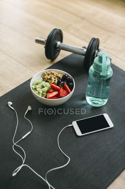 Haltere, garrafa de bebida, fruteira e smartphone com fones de ouvido — Fotografia de Stock