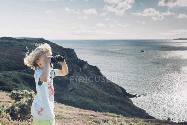 France, Brittany, Atlantic, boy looking through binoculars at the coast — Stock Photo