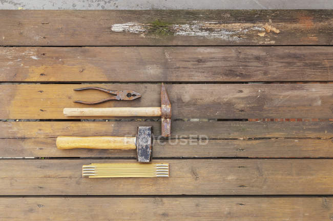 Row of four tools lying on rotten balcony floarboards — Stock Photo