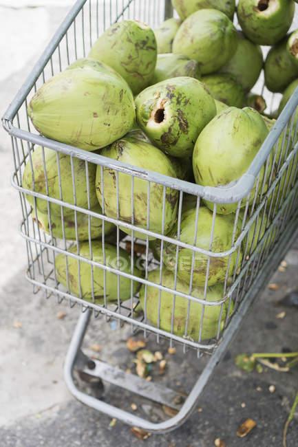Primer plano del carrito de la compra de cocos verdes - foto de stock