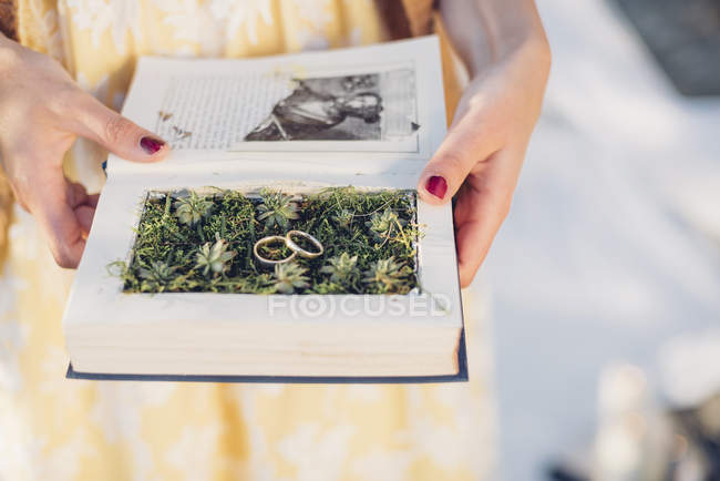 Woman's hands holding prepared book with two wedding rings lying on moss — Stock Photo