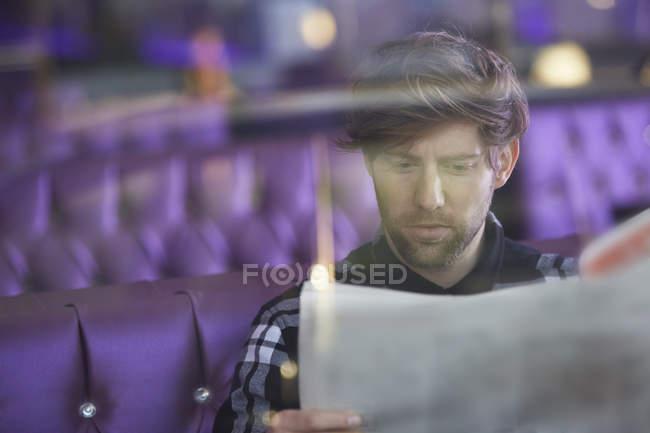 Lächelnde junge Mann sitzt in einer Lounge-Bar lesen Zeitung — Stockfoto