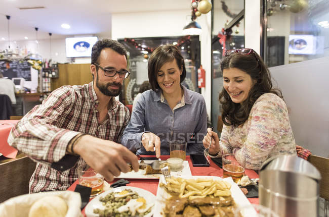 Three friends eating Spanish food in bar — Stock Photo