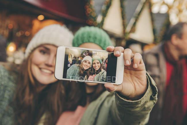Deux femmes heureuses prenant un selfie sur le marché de Noël — Photo de stock