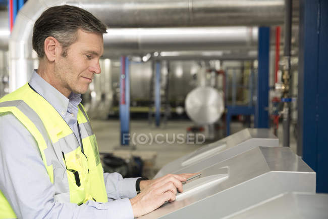 Technician operating control of industrial plant — Stock Photo