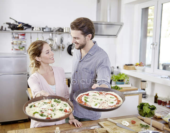 Couple holding baking pans with raw pizzas in kitchen — Stock Photo