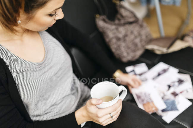 Young woman with cup of coffee  watching photos at home — Stock Photo
