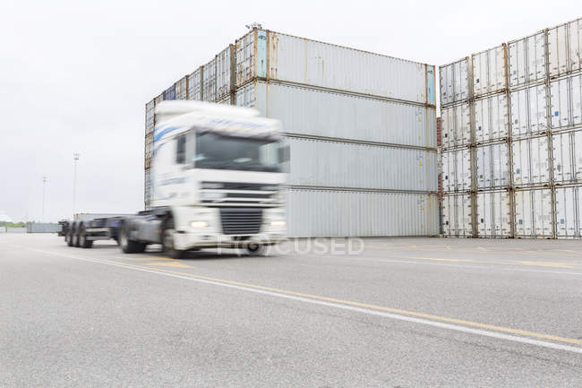 Stack of containers and passing truck — Stock Photo