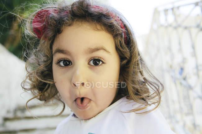 Портрет маленькой девочки, торчащей языком — стоковое фото