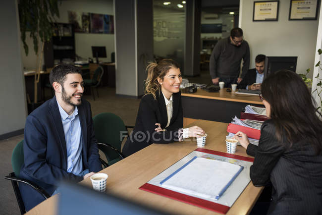 Smiling colleagues in office working together — Stock Photo