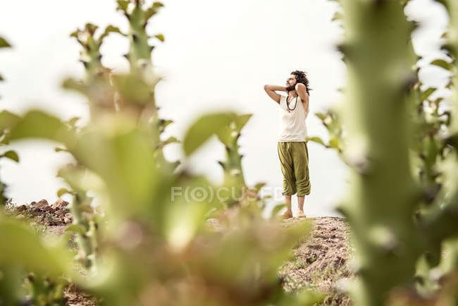 Uomo in piedi su roccia dietro cactus — Foto stock