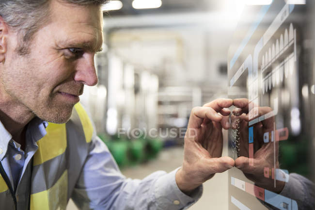 Man using touchscreen device in industrial plant — Stock Photo