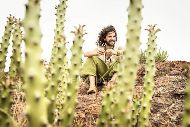 Man sitting on rock behind cacti — Stock Photo