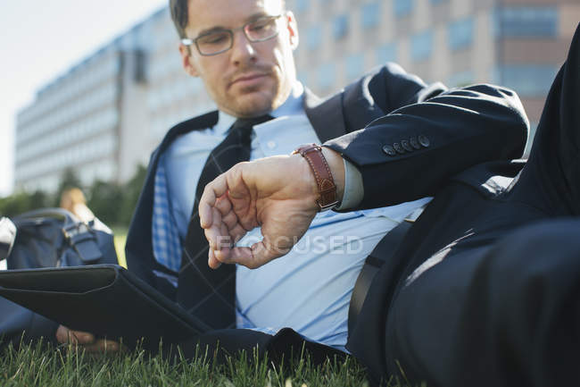 Businessman resting on meadow with digital tablet checking the time — Stock Photo