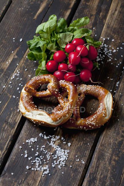 Dois biscoitos, rabanetes vermelhos e grãos de sal dispersados em madeira escura — Fotografia de Stock