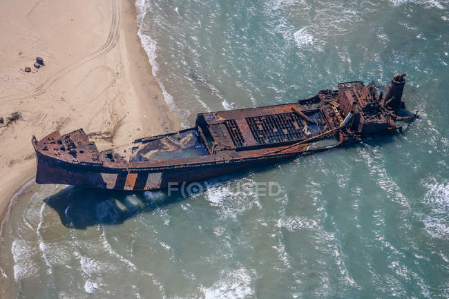 Italy, Lesina, stranded ship wreck at seafront seen from above — Stock Photo