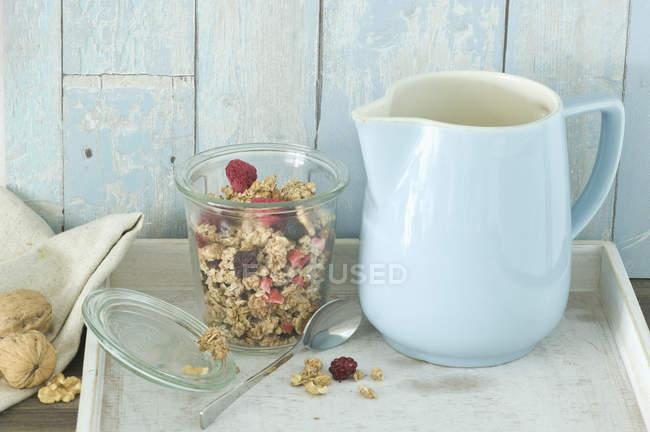 Copo de granola com blueberries secas e framboesas e um jarro de leite — Fotografia de Stock
