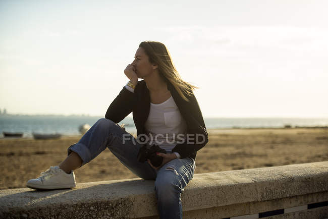 Woman relaxing on a wall in front of the beach — Stock Photo
