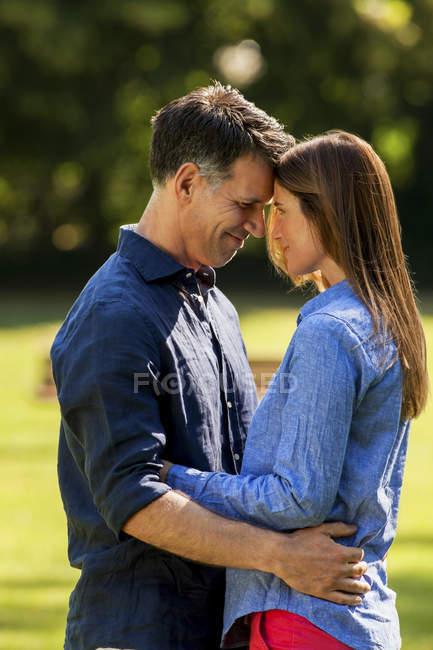 Счастливая кавказская пара, обнимающаяся в парке — стоковое фото
