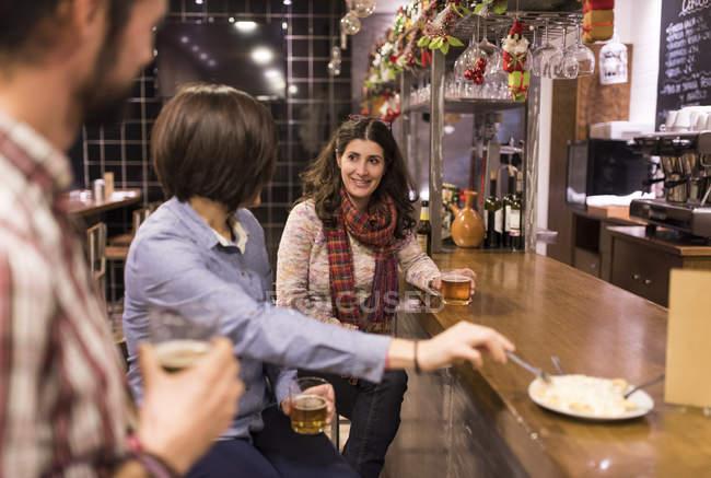 Три улыбаясь друзьям говорить в бар — стоковое фото