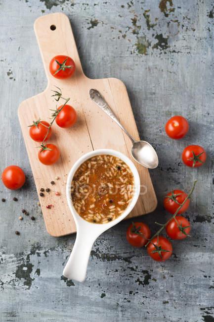 Ciotola di zuppa di pomodoro e riso sul tagliere — Foto stock