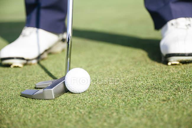 Nahaufnahme eines Golfspielers, der bereit ist, einen Golfball auf dem Grün eines Golfplatzes zu schlagen — Stockfoto