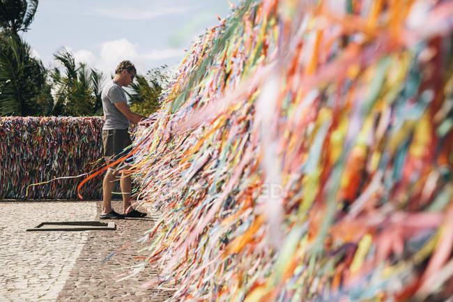 Brasile, Arraial d'Ajuda, uomo in piedi davanti al muro con nastri per il quincentenario del portoghese in Brasile — Foto stock