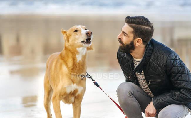 Homem observando seu cão baying — Fotografia de Stock