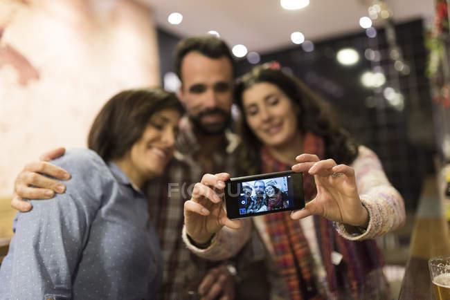 Três amigos tomando selfie em bar — Fotografia de Stock