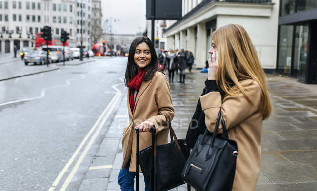Двоє друзів прогулянок по місту, за допомогою смартфона, Лондон, Великобританія — стокове фото