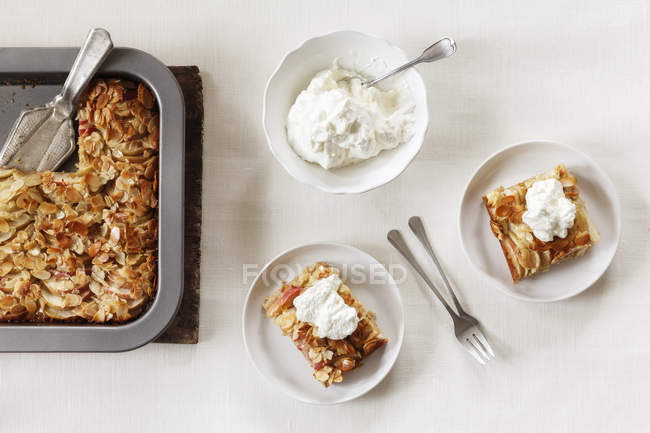 Pieces of whole meal apple pie with sliced almonds and whipped cream — Stock Photo