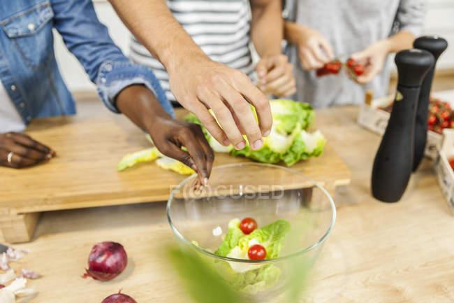Vista recortada de las personas que preparan ensalada - foto de stock