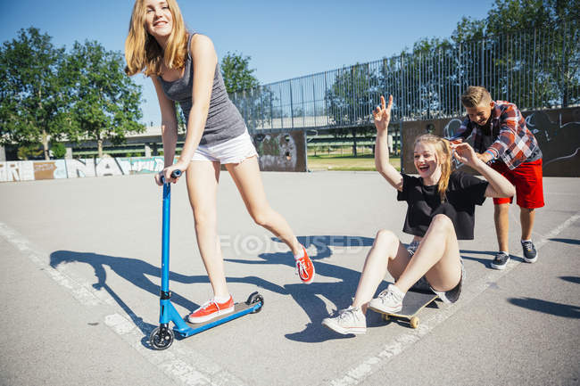 Three playful teenagers having fun with scooter and skateboard — Stock Photo