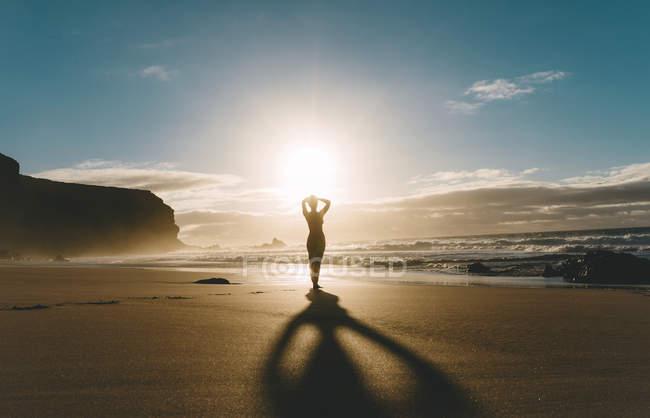 Mujer de pie en la playa con las manos en la cabeza al atardecer - foto de stock