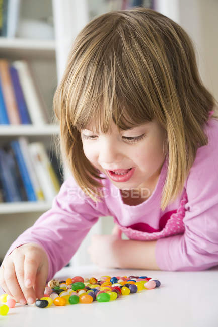 Portrait de jeune fille souriante, jouant avec les jujubes de rognée — Photo de stock