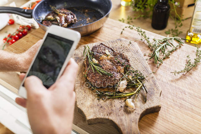 Man taking celll phone picture of prepared steaks — Stock Photo
