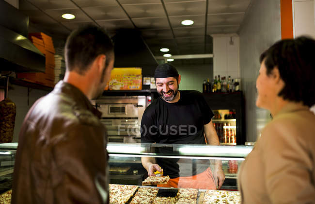 Couple choosing piece of pizza at snack bar — Stock Photo