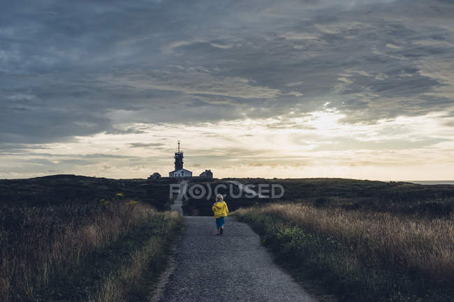 France, Brittany, Pointe du Raz, boy walking towards lighthouses Phare de la Vieille and Phare de Tevennec — Stock Photo